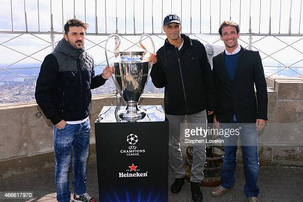David Villa Rivaldo and Juliano Belletti pose with the UEFA Champions League trophy on top of the Empire State Building on March 17 2015 in New York...