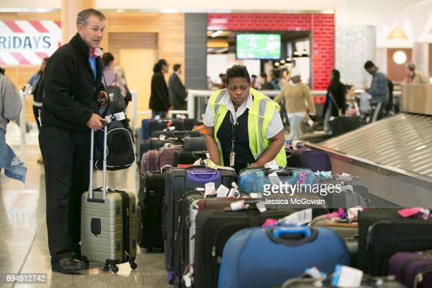 David Walker of Tifton Ga searches for his luggage at HartsfieldJackson Atlanta International Airport on December 18 2017 in Atlanta Georgia Hundreds...