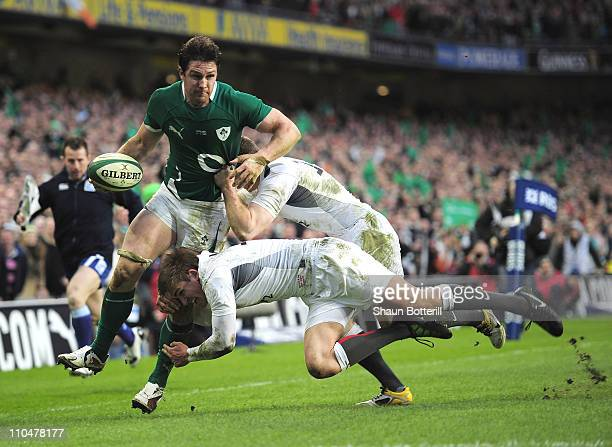 David Wallace of Ireland is tackled by Toby Flood and Chris Ashton of England during the RBS 6 Nations match between Ireland and England at the Aviva...