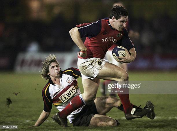 David Wallace of Munster charges through the challenge of Newport's James Ireland during the Celtic league match between Newport Gwent Dragons and...