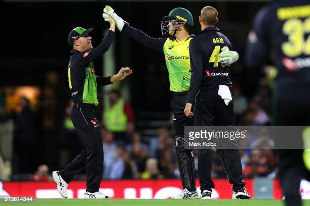 David Warner Alex Carey and Ashton Agar of Australia celebrate the wicket of Ross Taylor of New Zealand during game one of the International Twenty20...