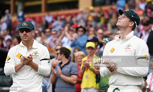David Warner of Australia and Steve Smith of Australia applaud during a minute's silence for the late Phillip Hughes during day one of the Third Test...