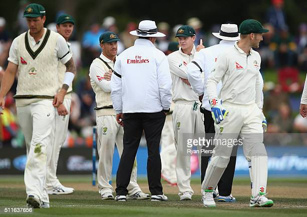 David Warner of Australia and Steve Smith of Australia speak to the umpires about a video review of a caught behind appeal against Henry Nicholls of...