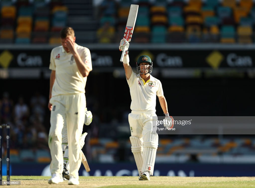 David Warner of Australia celebrates after reaching his half century as Jake Ball of England walks back to his mark during day four of the First Test Match of the 2017/18 Ashes Series between Australia and England at The Gabba on November 26, 2017 in Brisbane, Australia.