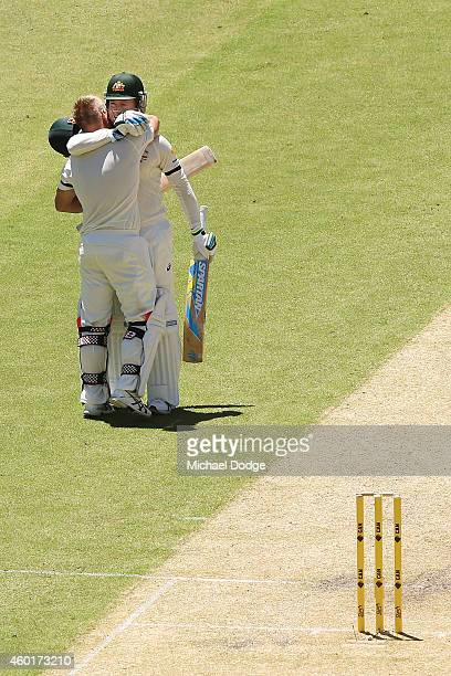 David Warner of Australia celebrates making his century with Michael Clarke during day one of the First Test match between Australia and India at...