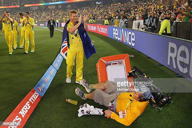 David Warner of Australia celebrates winning as a cameraman falls in front of him during the 2015 ICC Cricket World Cup final match between Australia...