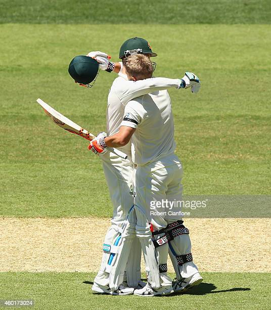 David Warner of Australia celebrates with Michael Clarke after reaching his century during day one of the First Test match between Australia and...
