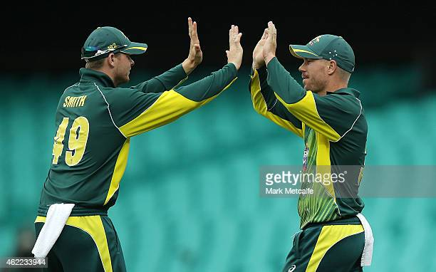David Warner of Australia celebrates with team mate Steven Smith after taking a catch to dismiss Ambati Rayudu of India off the bowling of Mitchell...