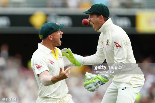 David Warner of Australia celebrates with team mate Tim Paine after taking a catch to dismiss Jake Ball of England during day two of the First Test...