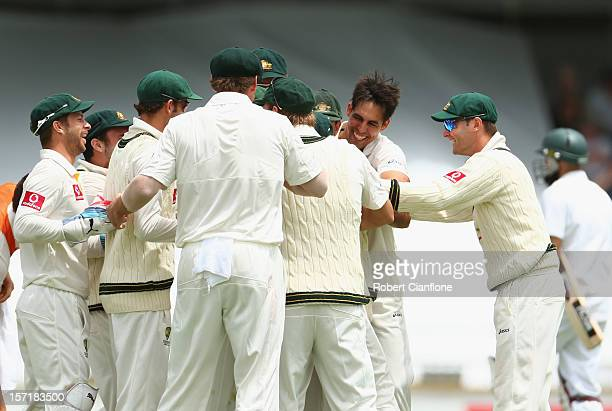 David Warner of Australia celebrates with team mates taking the run out of Hashim Amla of South Africa during day one of the Third Test Match between...