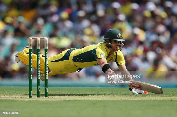 David Warner of Australia dives to make his ground during the fourth oneday international cricket match between India and Australia in Sydney on...