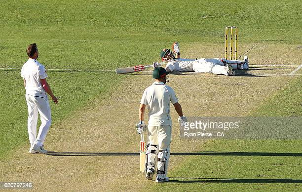 David Warner of Australia falls to the ground after hitting a six off Dale Steyn of South Africa during day one of the First Test match between...