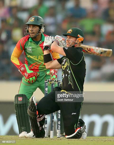David Warner of Australia hits a boundary as Mushfiqur Rahim of Bangladesh looks on during the ICC World Twenty20 Bangladesh 2014 match between...