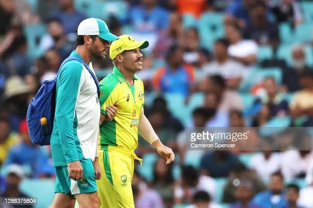 David Warner of Australia is assisted from the field after injuring himself during game two of the One Day International series between Australia and...