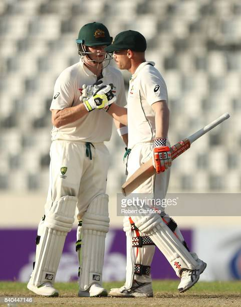David Warner of Australia is congratulated by Steve Smith after scoring his half century during day three of the First Test match between Bangladesh...