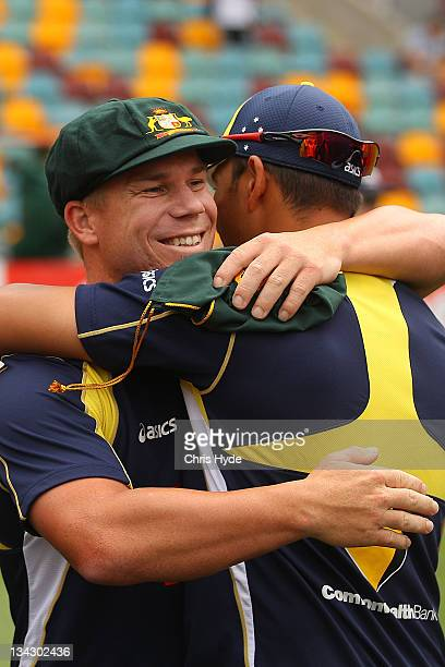David Warner of Australia is congratulated by Usman Khawaja after receiving his first test cap before play on day one of the First Test match between...