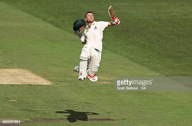 David Warner of Australia leaps in the air as he celebrates reaching his century during day three of the Second Test match between Australia and...