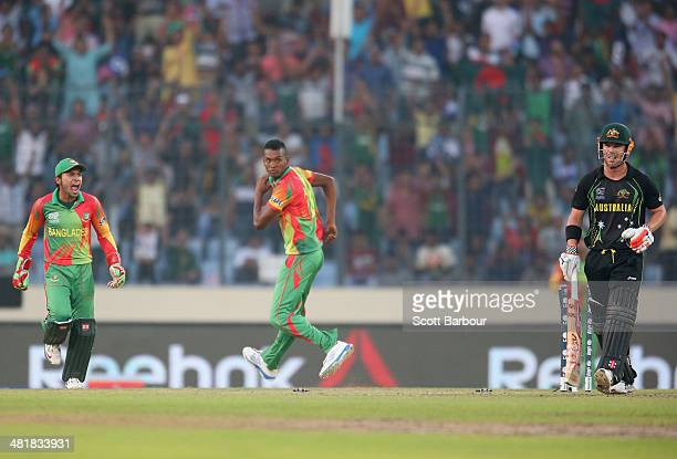 David Warner of Australia leaves the field after being bowled out by AlAmin Hossain of Bangladesh as Mushfiqur Rahim yells during the ICC World...