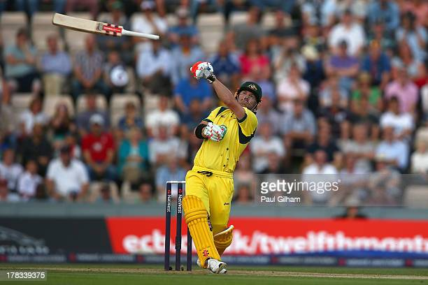 David Warner of Australia lets go of his bat as he hits out only to be caught out by Jos Buttler of England for 1 run off the bowling of Stuart Broad...