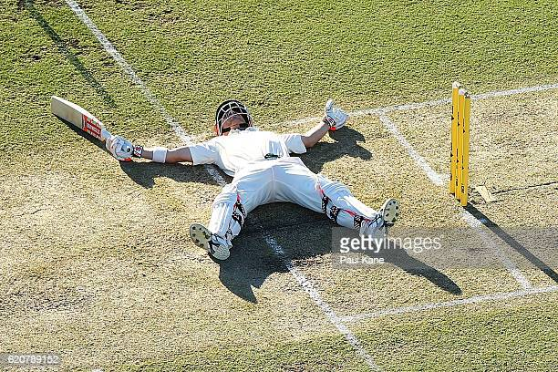 David Warner of Australia lies on the pitch after slipping while playing a shot during day one of the First Test match between Australia and South...