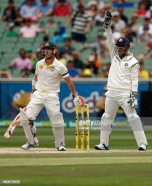 David Warner of Australia looks on as MS Dhoni of India appeals to the umpire during day four of the Third Test match between Australia and India at...