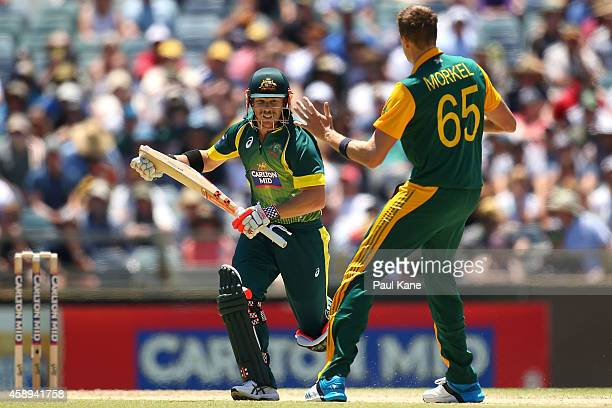 David Warner of Australia looks to avoid a collision with Morne Morkel of South Africa while taking a single during game one of the men's one day...