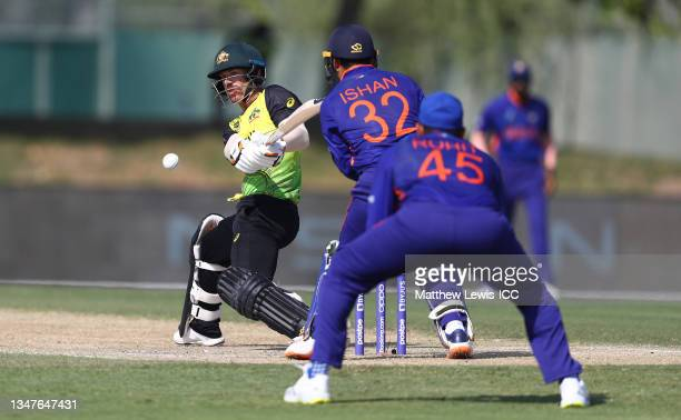 David Warner of Australia plays a shot as Ishan Kishan of India looks on during the India and Australia warm Up Match prior to the ICC Men's T20...