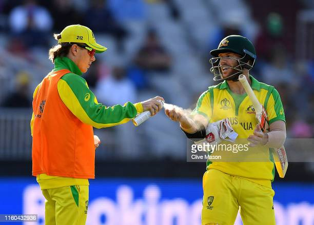David Warner of Australia receives treatment from a team member during the Group Stage match of the ICC Cricket World Cup 2019 between Australia and...