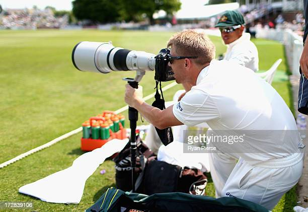 David Warner of Australia takes photos from the boundary during day three of the Tour Match between Worcestershire and Australia at New Road on July...