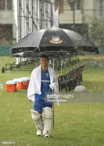 David Warner of Australia walks off the ground as rain falls during an Australian Test team nets session at SherE Bangla National Cricket Stadium on...