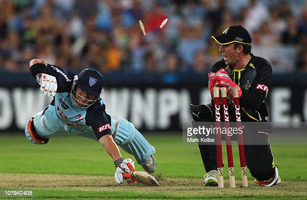 David Warner of the Blues dives as he is run out by Luke Ronchi of the Warriors during the Twenty20 Big Bash match between the New South Wales Blues...