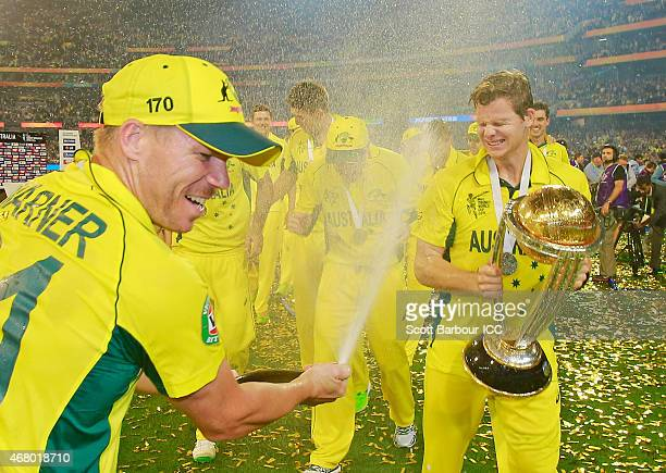 David Warner sparys champagne on Steven Smith of Australia as he holds the World Cup trophy aloft as Australia celebrate winning the 2015 ICC Cricket...