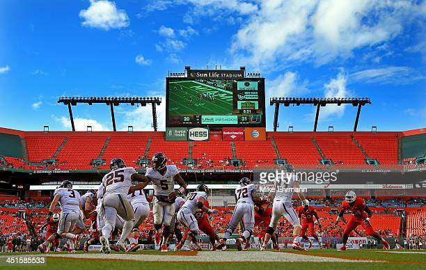 David Watford of the Virginia Cavaliers hands off to Kevin Parks during a game against the Virginia Cavaliers at Sun Life Stadium on November 23,...