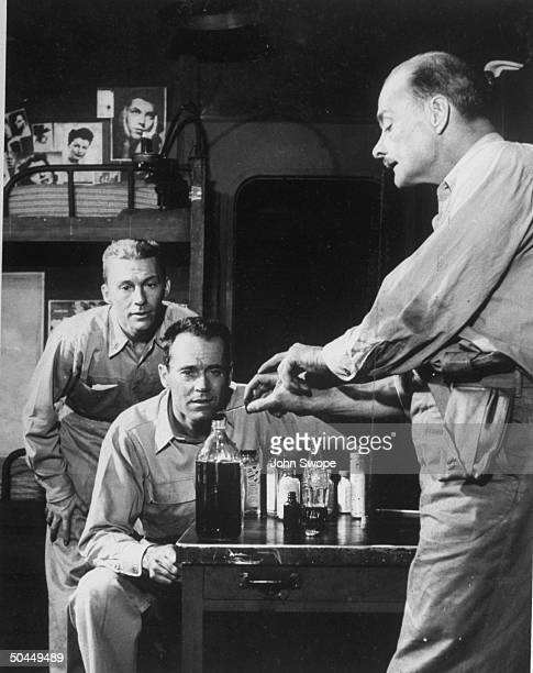 David Wayne and Henry Fonda watching Keith Robert demonstrate how to make scotch in a scene from Mister Roberts