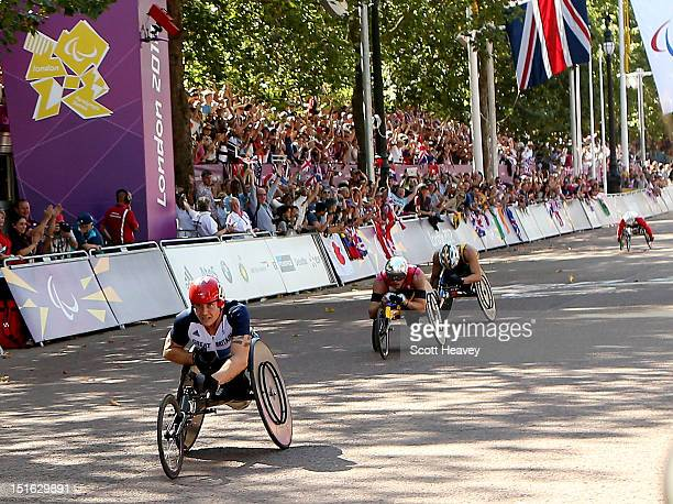 David Weir of Great Britain crosses the finishing line to win the T54 Men's Marathon on day 11 of the London 2012 Paralympic Games on The Mall on...