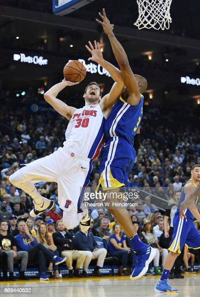 David West of the Golden State Warriors goes up to block the shot of Jon Leuer of the Detroit Pistons during an NBA basketball game at ORACLE Arena...