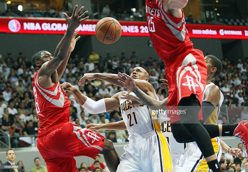 David West #21 of the Indiana Pacers fights for a rebound between Terence Jones #6 and Chandler Parsons #25 of the Houston Rockets during the NBA game between at the Mall of Asia Arena on October 10, 2013 in Manila, Philippines.