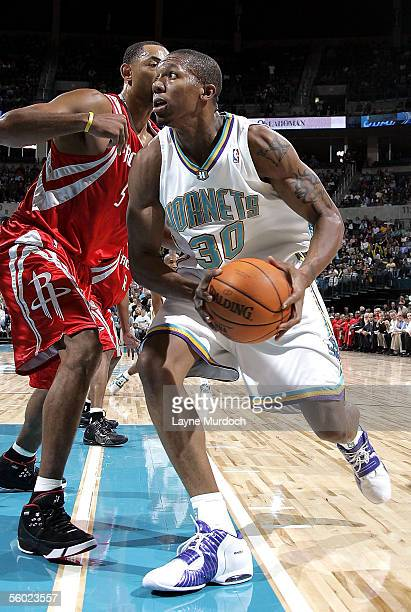 David West of the New Orleans/Oklahoma City Hornets drives past Juwan Howard of the Houston Rockets during a preseason game on October 27 2005 at the...