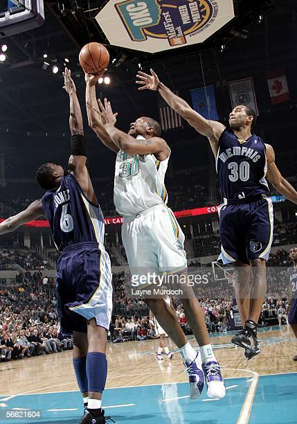 David West of the New Orleans/Oklahoma City Hornets shoots a jumper against Eddie Jones and Dahntay Jones of the Memphis Grizzlies on January 18 2006...