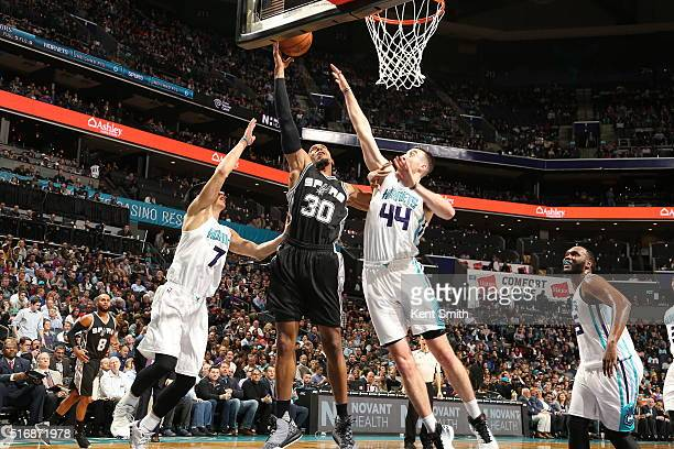 David West of the San Antonio Spurs goes to the basket against Frank Kaminsky III of the Charlotte Hornets and Jeremy Lin of the Charlotte Hornets on...