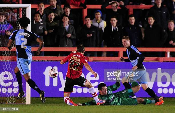 David Wheeler of Exeter City scores his side's first goal past Matt Ingram of Wycombe Wanderers during the Sky Bet League Two match between Exeter...