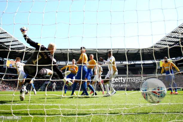 David Wheeler of Milton Keynes Dons scores his team's first goal past Conrad Logan of Mansfield Town during the Sky Bet League Two match between...