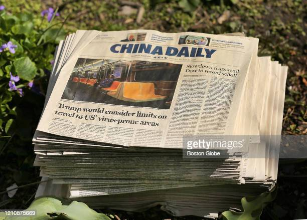 David Wiegman uses China Daily newspapers as a weed barrier in the soil before placing mulch on top at the garden of the Old South Church on Boylston...