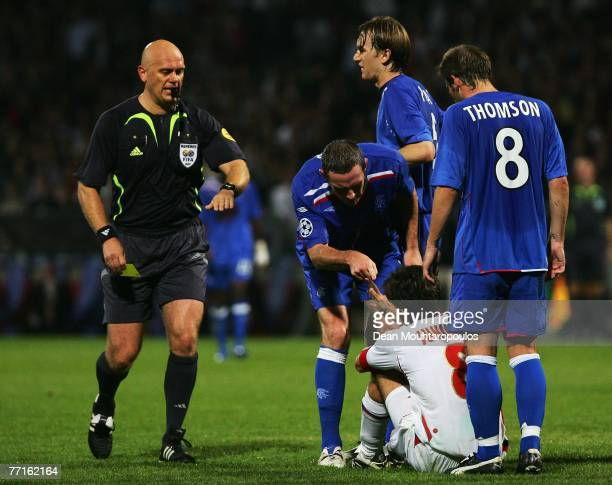 David Wier of Rangers points his finger at Juninho of Lyon after referee Tom Henning Ovvrebo showed the Rangers player a yellow card during the UEFA...