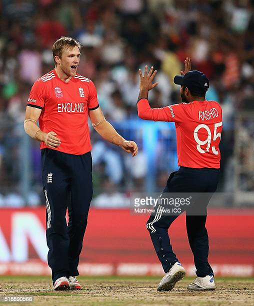 David Willey of England is congratulated by Adil Rashid of England on the wicket of Darren Sammy Captain of the West Indies after he was caught by...