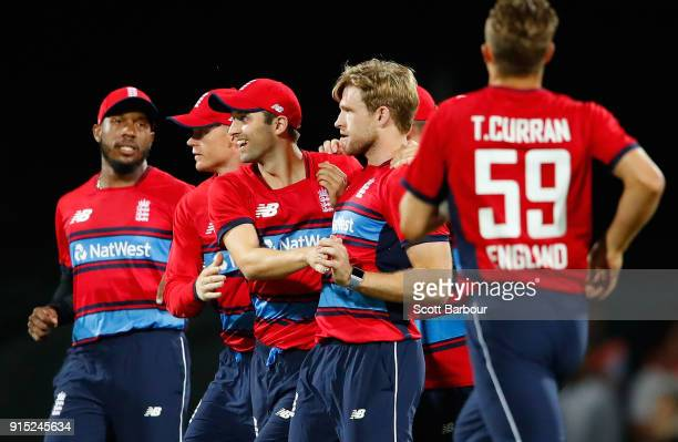 David Willey of England is congratulated by his teammates after dismissing David Warner of Australia during the Twenty20 International match between...