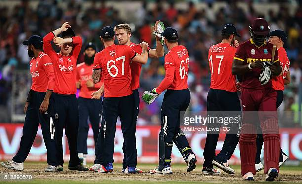 David Willey of England is congratulated on the wicket of Darren Sammy Captain of the West Indies after he was caught by Alex Hales of England during...