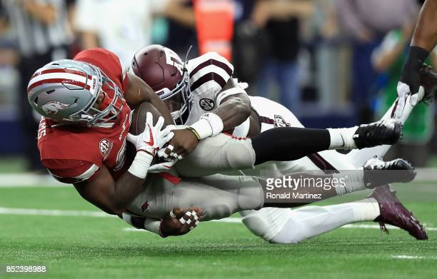 David Williams of the Arkansas Razorbacks is tackled by Debione Renfro of the Texas A&M Aggies in the first quarter at AT&T Stadium on September 23,...