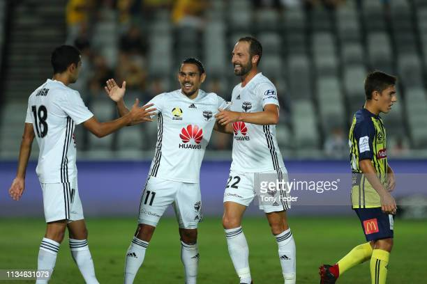 David Williams of Wellington Phoenix celebrates a goal with team mates Andrew Durante and Sarpreet Singh during the round 21 ALeague match between...