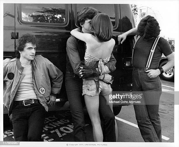 David Wilson embracing Donna Wilkes while Allen G Norman and John Kirby look on in a scene from the film 'Almost Summer' 1978